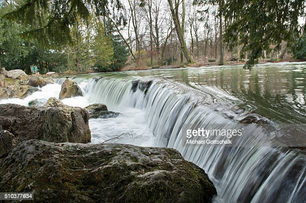 Waterfall of Eisbach river at Englischer Garten of English Gardens on February 15 2016 in Munich Germany