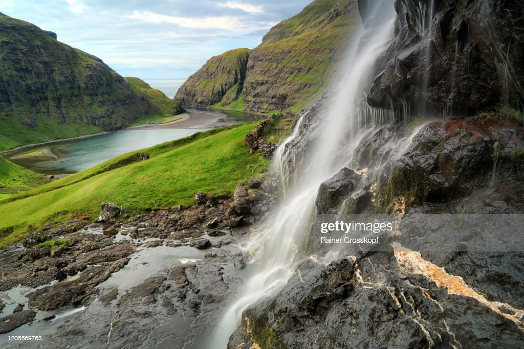 Waterfall over rocks high above a secluded bay between grassy mountains : Stock-Foto
