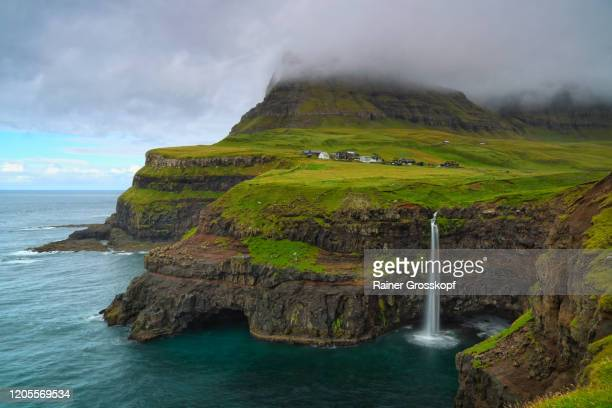 a waterfall over the cliffs into the sea near a small village surrounded by grassy mountains - rainer grosskopf stock-fotos und bilder