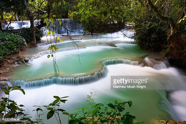 A waterfall running into an emerald pond.