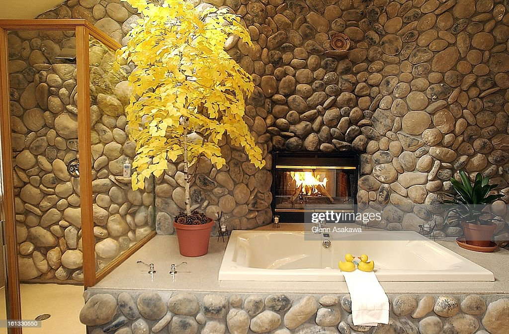 A waterfall shower, left, and jetted hot tub for two next to a ...