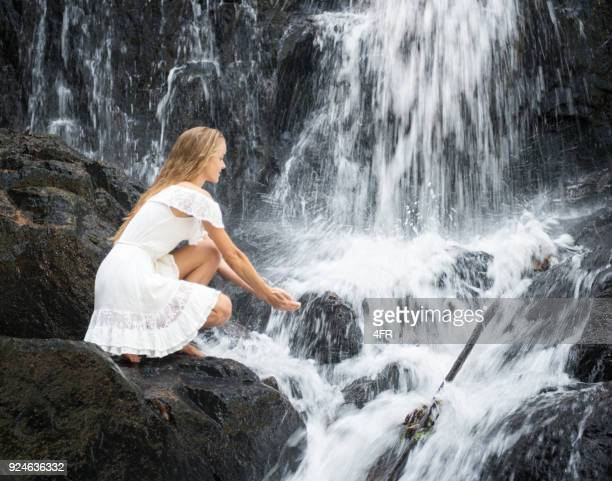 Waterfall Stream Fairy Tale, Beautiful Woman in a White Dress, catching water with her Hands