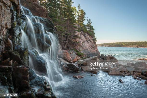 a waterfall tumbling into the atlantic ocean, cape breton highlands national park, nova scotia, canada - cape breton island stock pictures, royalty-free photos & images