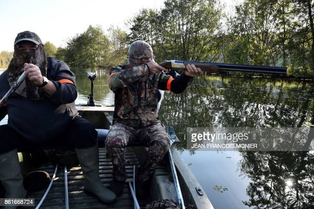 Waterfowl hunters steer a boat on Le Loir river during a duck hunting in Vaas northwestern France on October 15 2017 / AFP PHOTO / JEANFRANCOIS MONIER