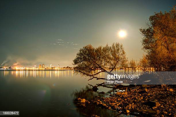Waterfront by moonlight with industrial horizon