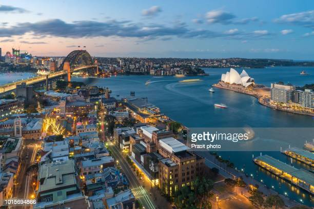 waterfront city skyline of sydney city downtown at night with bright illumination of modern architectural landmarks in sydney, australia. - sydney stock pictures, royalty-free photos & images