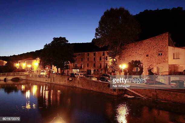 waterfront houses on river bank at night in small town of Lunas in department of Herault in Languedoc Roussillon France