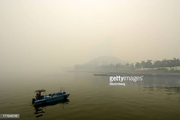 Waterfront river cleaners sit in their boat near the Marina Bay Sands hotel towers and the Sands Expo and Convention Center, center, as they stand...