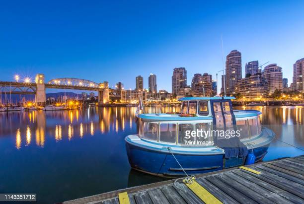 waterfront skyline and harbor illuminated at night, vancouver, british columbia, canada - schiffstaxi stock-fotos und bilder