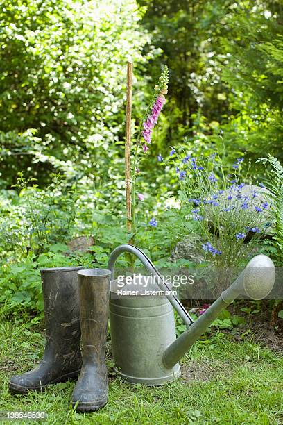 A watering can and a pair of rubber boots, outdoors