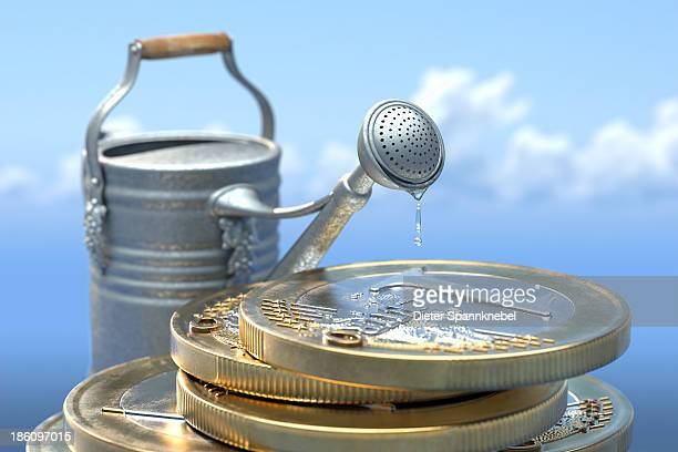 Watering can beside a stack of euro coins