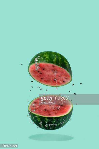 watermelon sliced flying on pastel green background. minimal fruit and summer concept. - watermelon stock pictures, royalty-free photos & images
