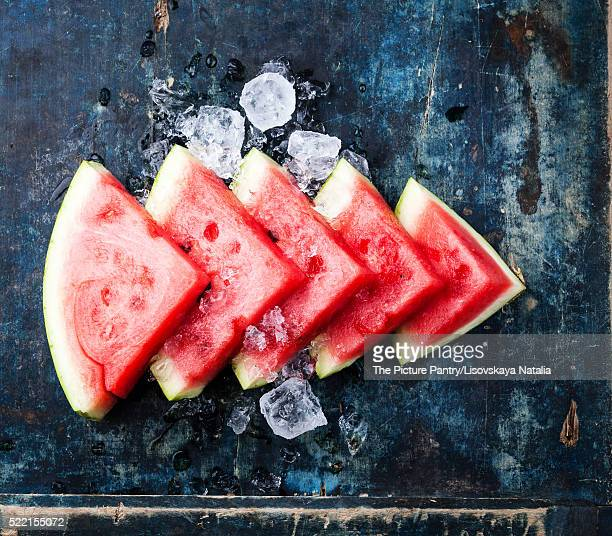 Watermelon slices and ice on blue background