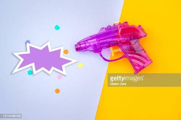 waterpistool op een gekleurde achtergrond - gekleurde achtergrond stock pictures, royalty-free photos & images