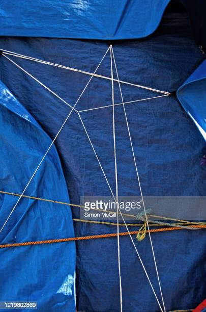 waterproof blue plastic tarps tied with ropes covering an object - tarpaulin stock pictures, royalty-free photos & images