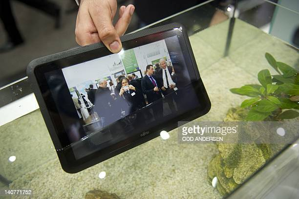 A waterproof tablet PC from Fujitsu is seen lowered into a fish tank at the world's biggest hightech fair the CeBIT on March 6 2012 in Hanover...