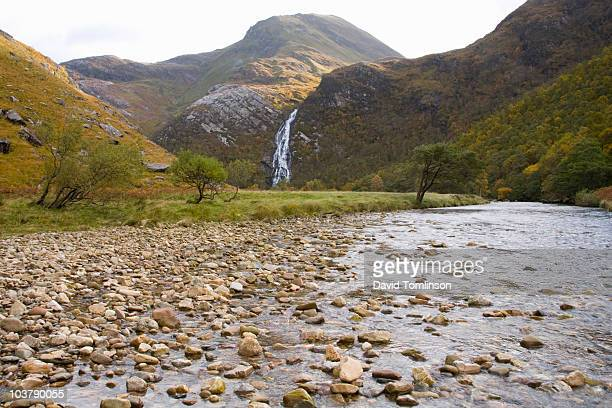waters of nevis with steall waterfall and peak of an gearanach at the head of glen nevis in autumn. - human face foto e immagini stock
