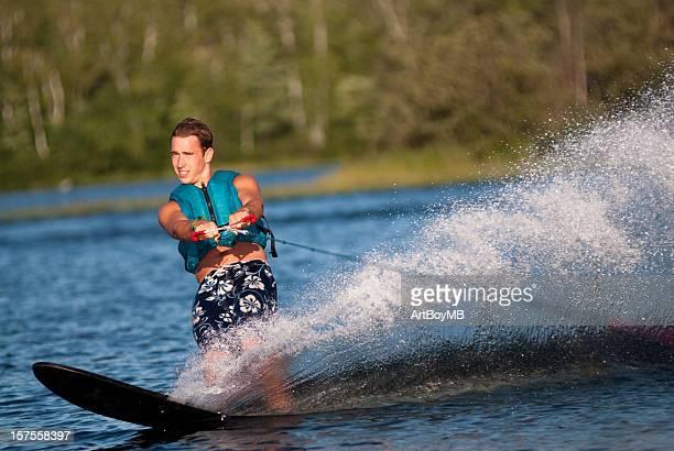 Waterskiing with man shredding waves