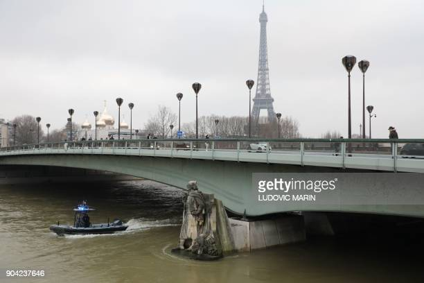 A waterway police boat patrols on the waters of the river Seine whose level has risen near the statue of the Zouave at the Alma bridge in Paris PHOTO...