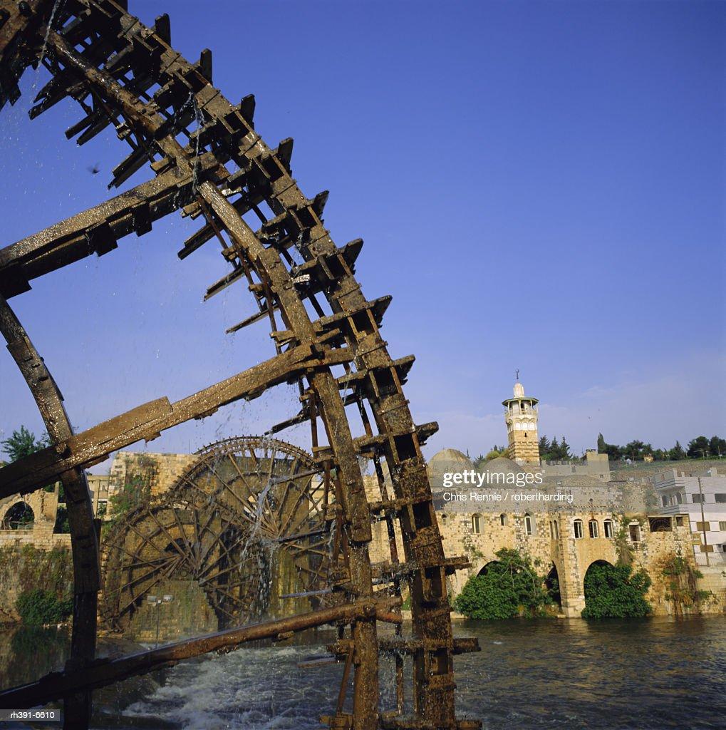 Waterwheels (norias) on Orontes River, Mosque al Nuri on far bank, Hama, Syria, Middle East : Stockfoto