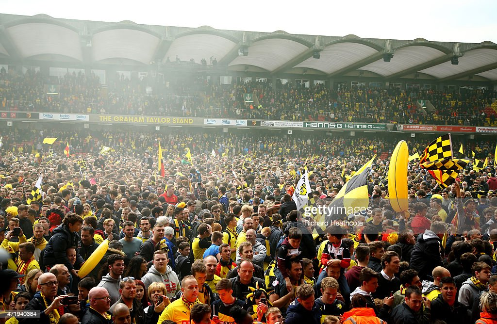 Watford fans celebrate promotion on the pitch after the Sky Bet Championship match between Watford and Sheffield Wednesday at Vicarage Road on May 2, 2015 in Watford, England.
