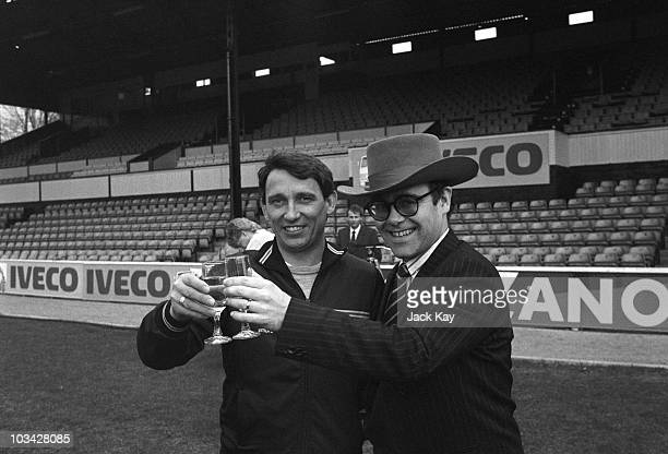 Watford FC manager Graham Taylor and Chairman Elton John share a drink on the Vicarage Road pitch in Watford England on April 11 1984