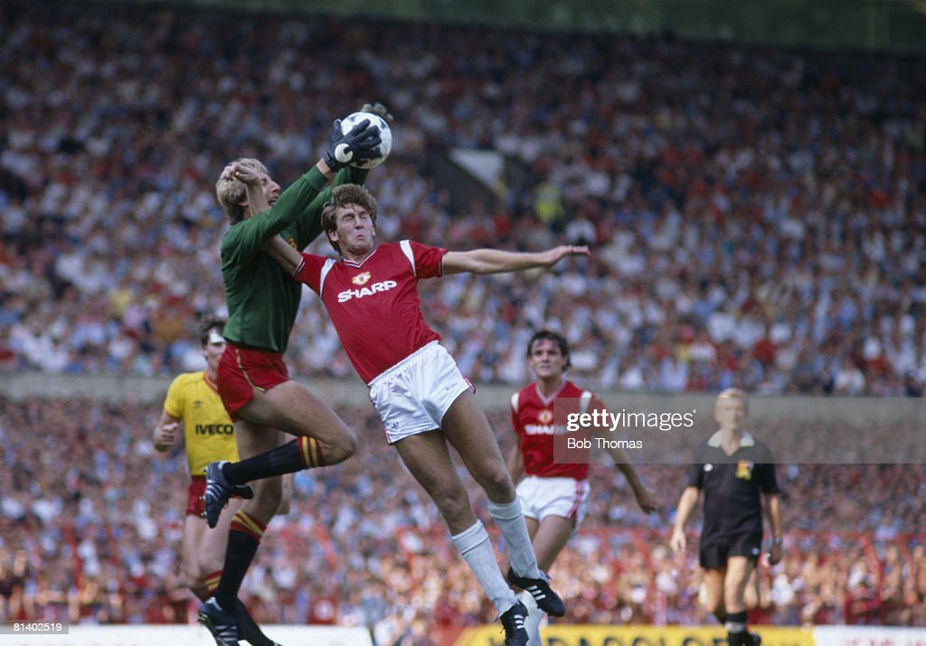 Watford goalkeeper Steve Sherwood catches the ball under pressure from Manchester United's Norman Whiteside during their 1st Division match at Old Trafford, 25th August 1984. The match ended in a 1-1 draw. (Photo by Bob Thomas/Getty Images).