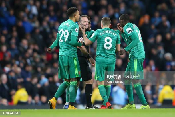 Watford players argue with referee Paul Tierney after Manchester City's first goal is given during the Premier League match between Manchester City...