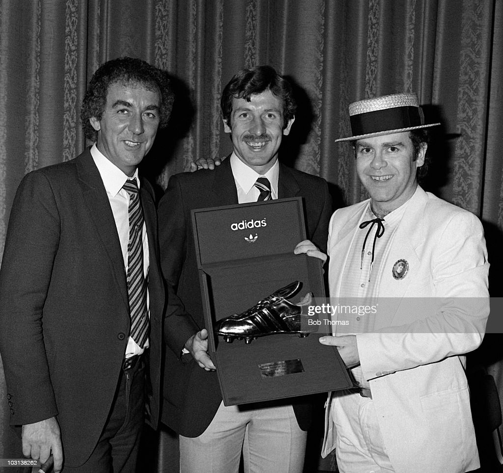 Watford striker Gerry Armstrong receives his Golden Boot, in recognition of his contribution to Northern Ireland's 1982 World Cup campaign, from Watford Chairman Elton John (right) and Comedian Lenny Bennett (left) at the Adidas Golden Boot award ceremony in London, 25th August 1982.