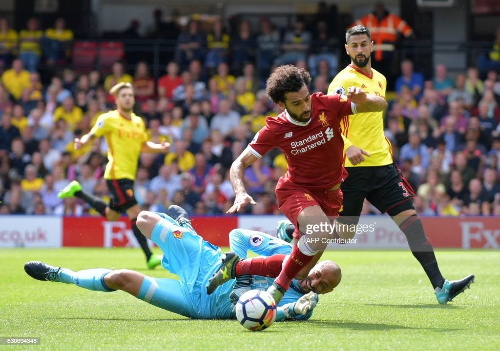 Watford's Brazilian goalkeeper Heurelho Gomes (L) fouls Liverpool's Egyptian midfielder Mohamed Salah to concede a penalty during the English Premier League football match between Watford and Liverpool at Vicarage Road Stadium in Watford, north of London on August 12, 2017. / AFP PHOTO / OLLY GREENWOOD / RESTRICTED TO EDITORIAL USE. No use with unauthorized audio, video, data, fixture lists, club/league logos or 'live' services. Online in-match use limited to 75 images, no video emulation. No use in betting, games or single club/league/player publications. /