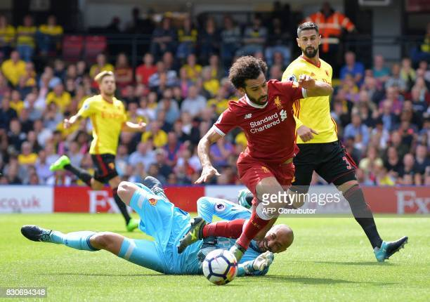 Watford's Brazilian goalkeeper Heurelho Gomes fouls Liverpool's Egyptian midfielder Mohamed Salah to concede a penalty during the English Premier...