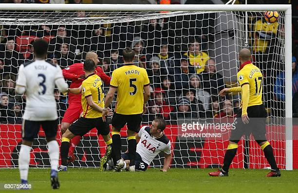 Watford's Brazilian goalkeeper Heurelho Gomes reacts as Tottenham Hotspur's English striker Harry Kane falls to the ground after scoring his team's...