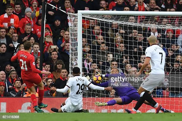 TOPSHOT Watford's Brazilian goalkeeper Heurelho Gomes saves a shot from Liverpool's Brazilian midfielder Lucas Leiva during the English Premier...