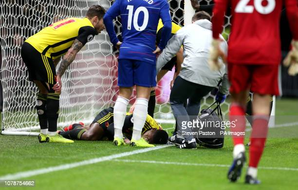 Watford's Christian Kabasele receives medical treatment on the pitch after colliding with the goalpost