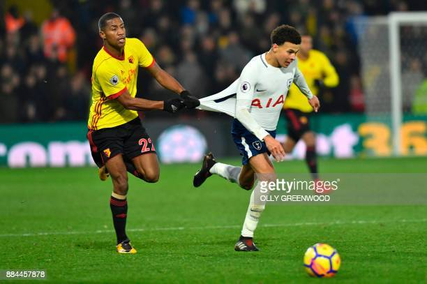 Watford's Dutch midfielder Marvin Zeegelaar pulls the shirt of Tottenham Hotspur's English midfielder Dele Alli during the English Premier League...