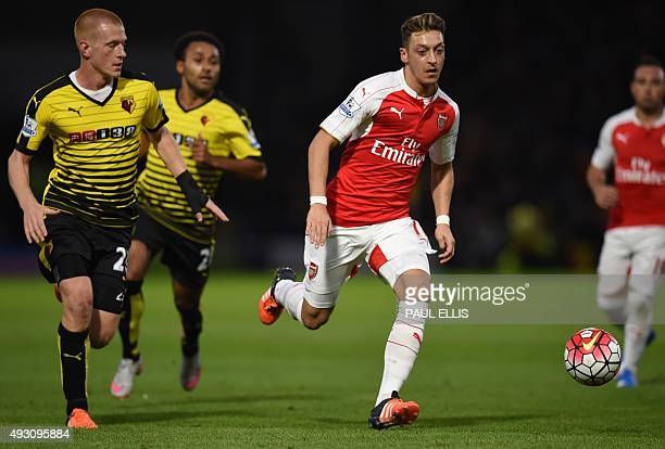 Watford's English midfielder Ben Watson vies with Arsenal's German midfielder Mesut Ozil during the English Premier League football match between...