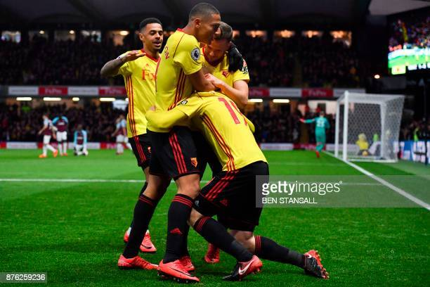 Watford's English midfielder Will Hughes celebrates scoring the opening goal with teammates during the English Premier League football match between...