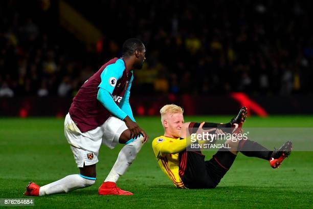 Watford's English midfielder Will Hughes holds his leg after being fouled by West Ham United's Spanish midfielder Pedro Obiang an offence for which...