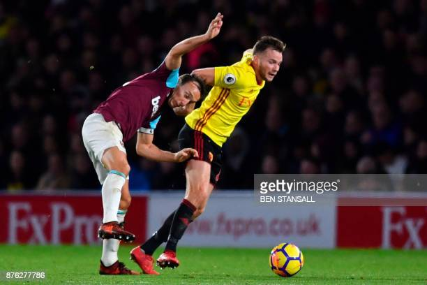 Watford's English mifielder Tom Cleverley holds off West Ham United's English midfielder Mark Noble during the English Premier League football match...