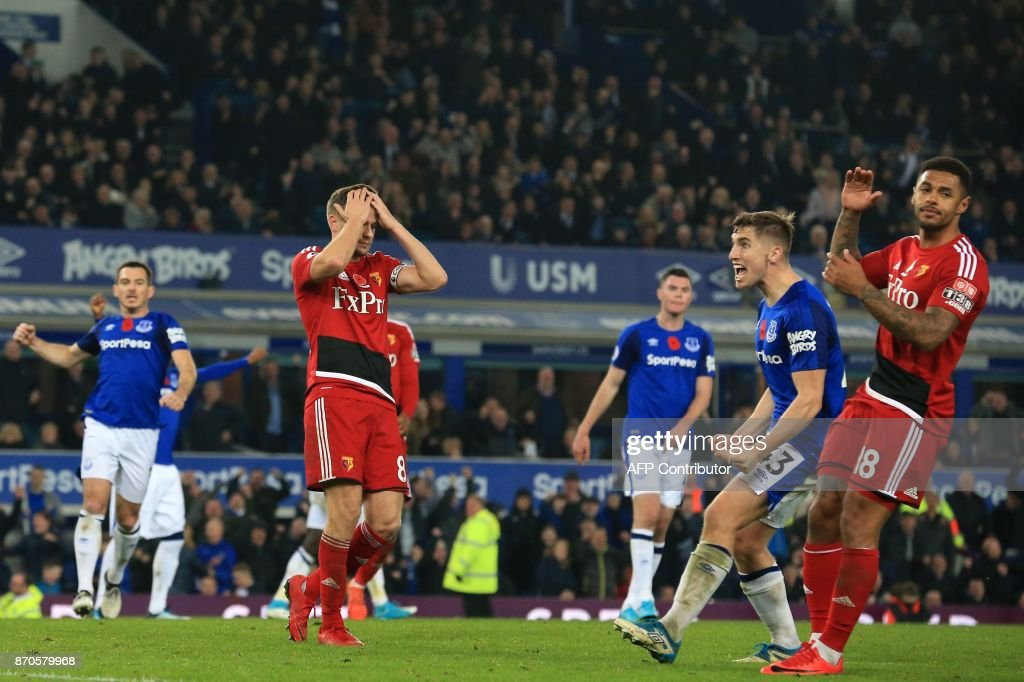 Watford's English mifielder Tom Cleverley (C) reacts after failing to score from the penalty spot in the final moments of the English Premier League football match between Everton and Watford at Goodison Park in Liverpool, north west England on November 5, 2017. Everton won the game 3-2. / AFP PHOTO / Lindsey PARNABY / RESTRICTED TO EDITORIAL USE. No use with unauthorized audio, video, data, fixture lists, club/league logos or 'live' services. Online in-match use limited to 75 images, no video emulation. No use in betting, games or single club/league/player publications. /