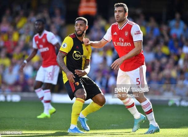 Watford's English striker Andre Gray and Arsenal's Greek defender Sokratis Papastathopoulos look on during the English Premier League football match...
