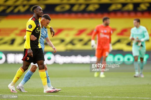 Watford's English striker Danny Welbeck and Manchester City's English midfielder Phil Foden embrace as they walk off after the English Premier League...