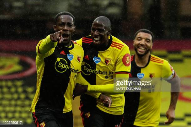 Watford's English striker Danny Welbeck celebrates with Watford's French midfielder Abdoulaye Doucoure after scoring his team's second goal during...