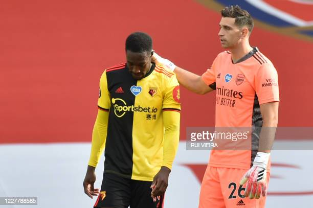 Watford's English striker Danny Welbeck is consoled by Arsenal's Argentinian goalkeeper Emiliano Martinez after losing the English Premier League...