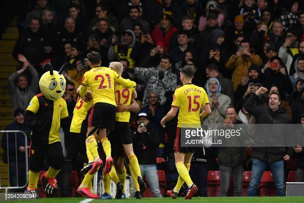 Watford's English striker Troy Deeney celebrates with teammates after scoring his team's third goal during the English Premier League football match...