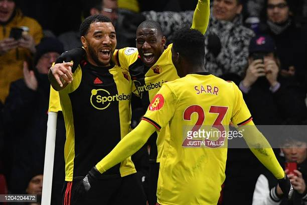 Watford's English striker Troy Deeney celebrates with Watford's French midfielder Abdoulaye Doucoure after scoring his team's third goal during the...