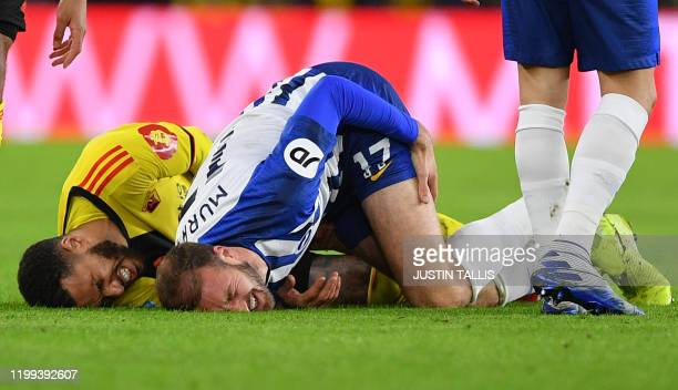 Watford's French midfielder Etienne Capoue and Brighton's English striker Glenn Murray go down after a tackle during the English Premier League...