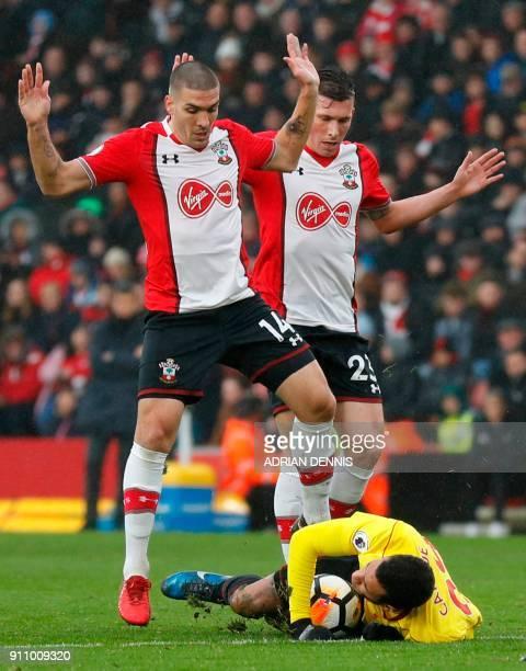 Watford's French midfielder Etienne Capoue goes down as Southampton's Spanish midfielder Oriol Romeu and Southampton's Danish midfielder PierreEmile...