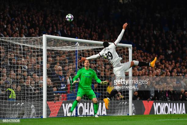 TOPSHOT Watford's French midfielder Etienne Capoue heads the ball as Chelsea's Bosnian goalkeeper Asmir Begovic keeps goal during the English Premier...