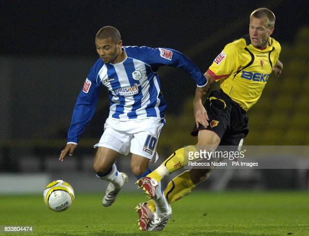 Watford's Gavin Mahon and Sheffield Wednesday's Deon Burton battle for the ball during the CocaCola Championship match at Vicarage Road Watford